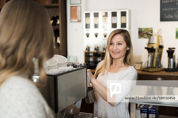 Barista bei der Arbeit in der Kommunikation mit dem Kunden