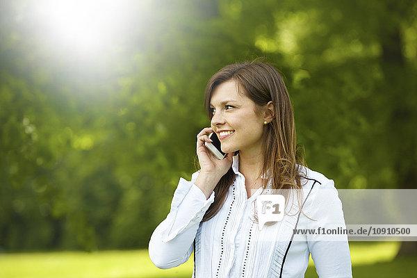 Lächelnde junge Frau telefoniert mit Smartphone im Park