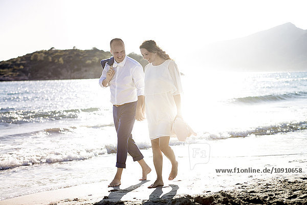 Spanien  Mallorca  schwangere Frau und Mann beim Spaziergang am Strand