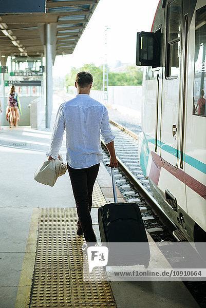 Junger Mann  der den Zug an einem Bahnhof verlässt.