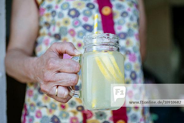 Nahaufnahme einer Frau mit einem Glas Limonade Nahaufnahme einer Frau mit einem Glas Limonade