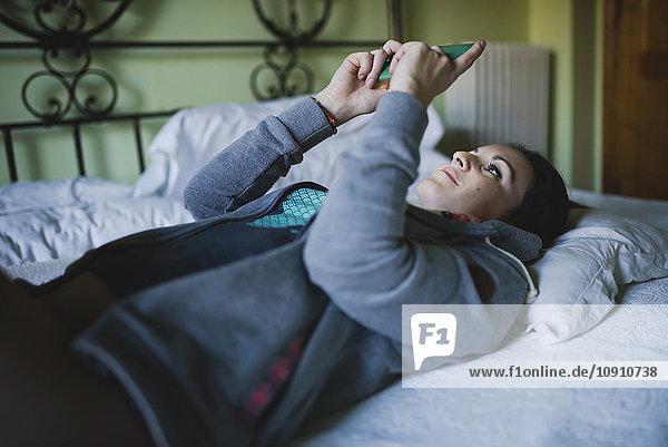 Frau im Bett liegend mit Smartphone