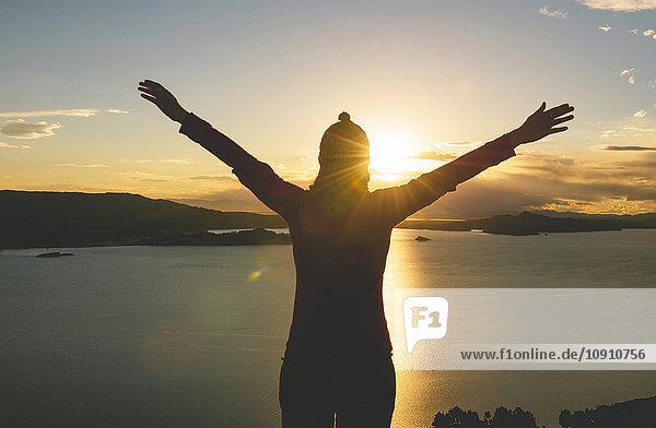 Peru  Insel Amantani  Silhouette einer Frau mit erhobenen Armen  die den Sonnenuntergang vom Gipfel des Pachamama genießt.