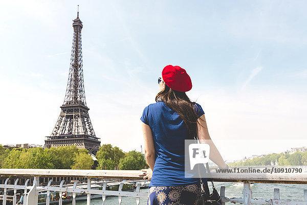 Frankreich  Paris  Rückansicht der Frau mit roter Baskenmütze beim Blick auf den Eiffelturm
