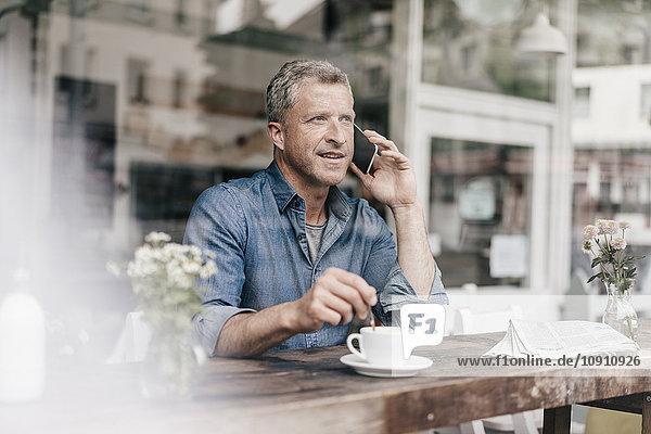 Ein reifer Mann  der im Café sitzt und telefoniert.