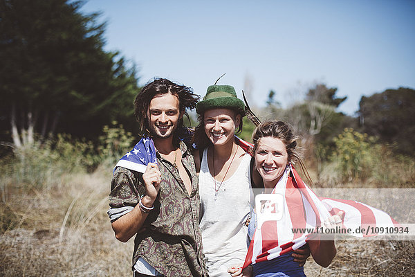 Porträt von drei lächelnden Hippies mit US-Flagge in der Natur