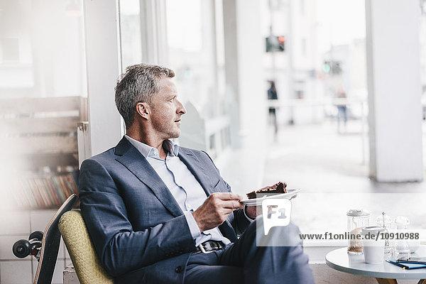 Businessman in cafe eating cake