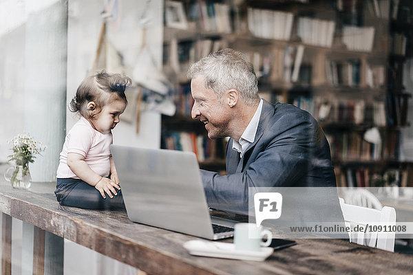 Geschäftsmann mit kleiner Tochter bei der Arbeit am Laptop im Cafe