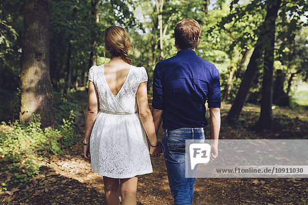 Back view of couple in love walking hand in hand in the forest