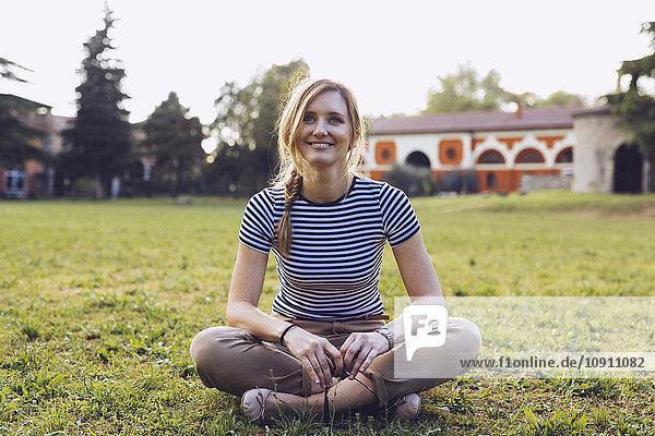 Porträt einer lächelnden Blondine auf einer Wiese sitzend