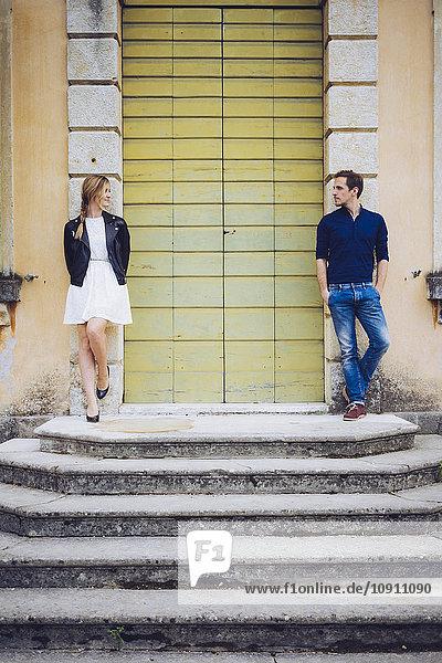 Italy  Verona  couple standing besides wooden door looking at each other