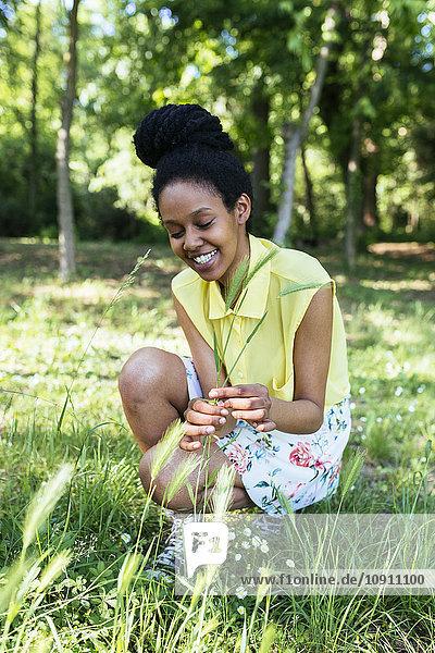 Porträt einer lächelnden jungen Frau beim Graspflücken