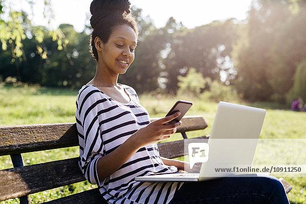 Junge Frau mit Laptop auf Parkbank mit Blick auf Smartphone