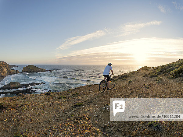 Portugal  Senior man mountain biking at the sea