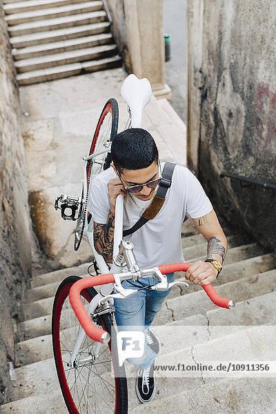 Junger Mann mit Fahrrad auf der Treppe