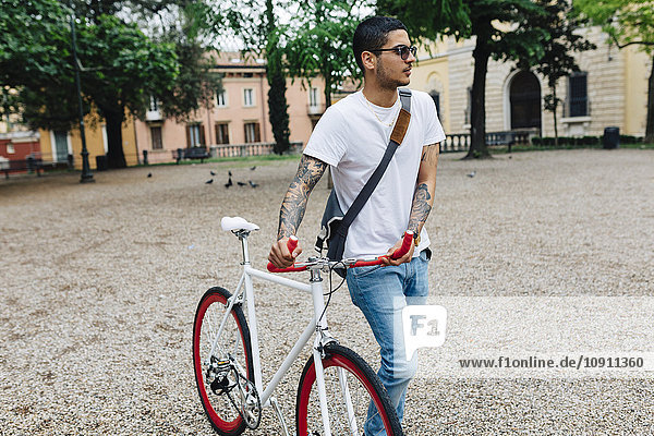 Young man walking with a bicycle in the city