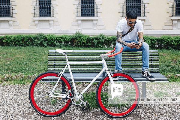 Junger Mann mit Fahrrad auf der Bank sitzend