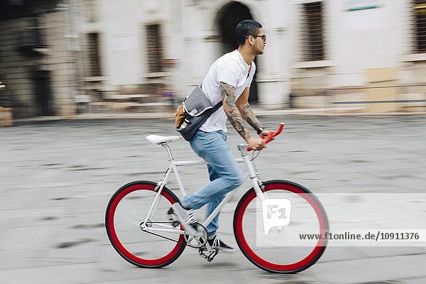 Junger Mann auf dem Fahrrad in der Stadt