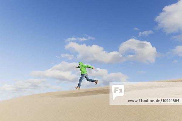 Mann rennt eine Sanddüne hinunter