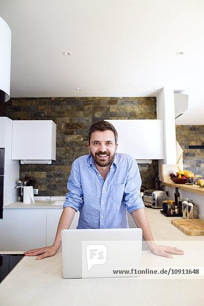 Mann arbeitet in der Küche mit Laptop