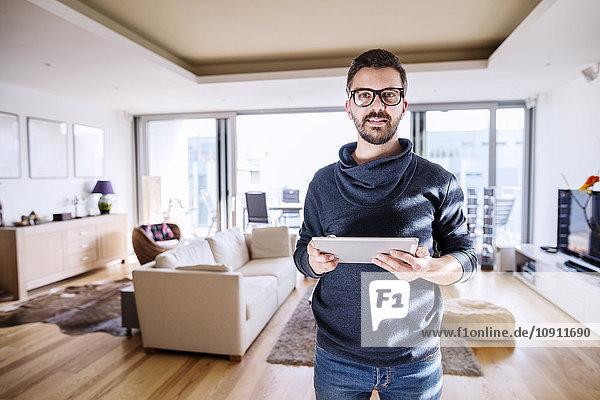 Man standing in living room  using digital tablet