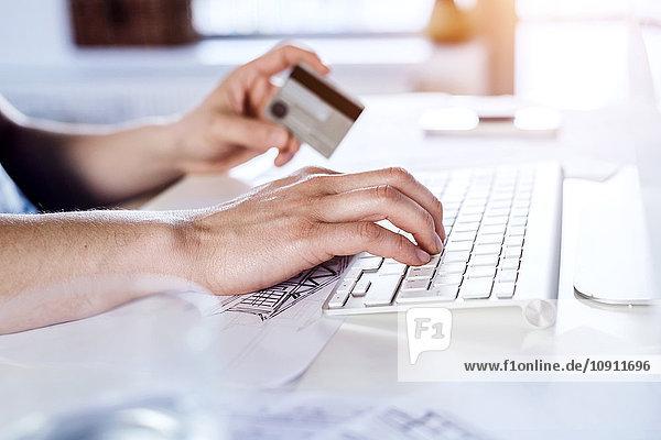 Mann bei der Online-Zahlung mit Kreditkarte