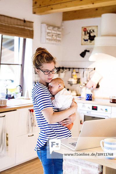 Mutter mit Baby in der Küche mit Blick auf Laptop