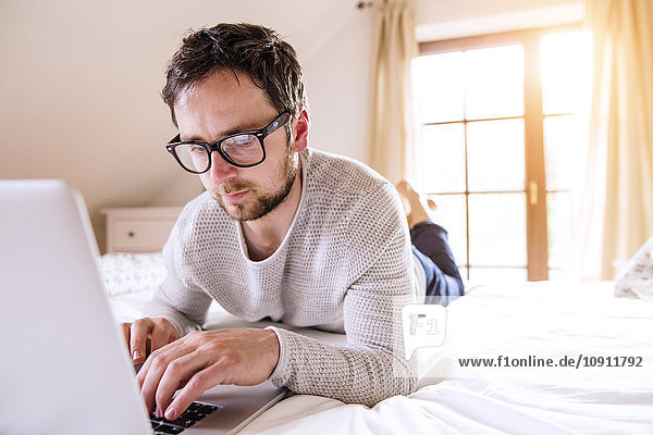 Mann auf dem Bett liegend mit Laptop