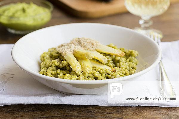 Risotto mit grünem Spargelpesto  weißen Spargelstangen und veganem Mandelparmesan