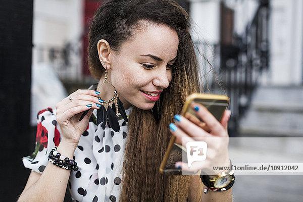 UK  London  junge Frau  die ihren Ohrring mit Hilfe ihres Smartphones beobachtet.