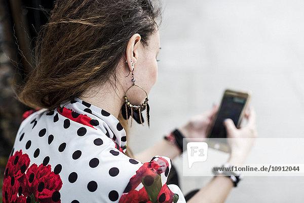 Rückansicht der jungen Frau mit ihrem Smartphone