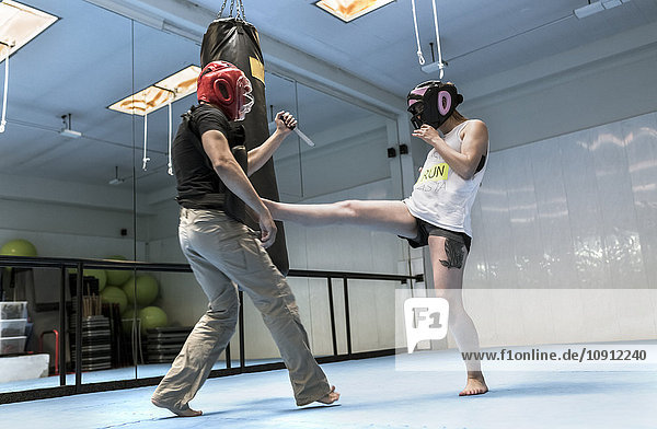 Junge Frau im Fitnessstudio beim Selbstverteidigungstraining