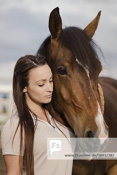 Junge Frau mit braunem Pferd im Freien