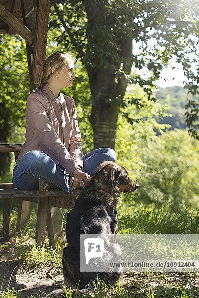 Junge Frau sitzt auf einer Holzbank und entspannt sich mit ihrem Hund.