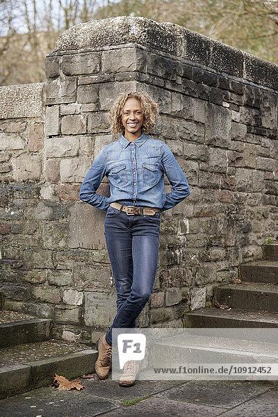 Porträt einer lächelnden Frau in Jeans und Denim-Shirt