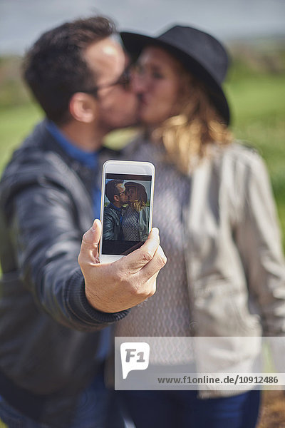 Selfie des küssenden Paares auf dem Display des Smartphones