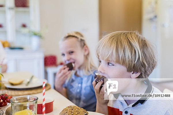 Glücklicher Junge am Tisch  der Schoko-Marshmallow isst. Glücklicher Junge am Tisch, der Schoko-Marshmallow isst.