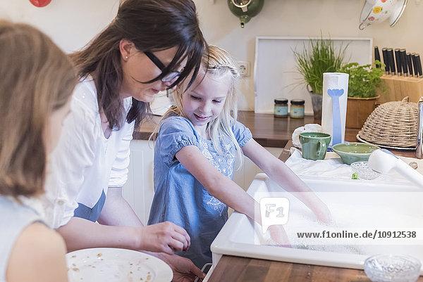 Mutter und zwei Mädchen beim Abwasch in der Küche