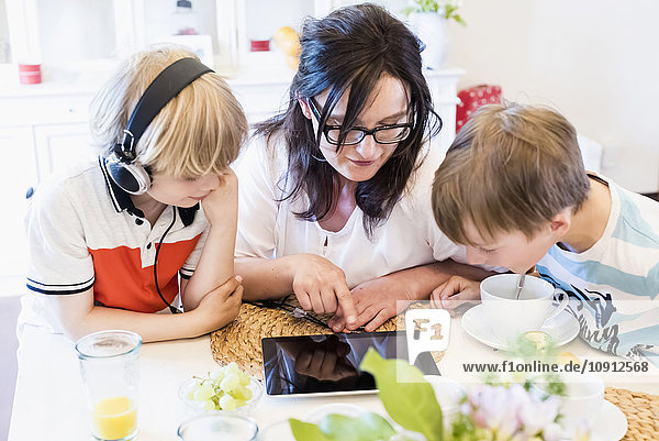 Mother and two boys sharing digital tablet