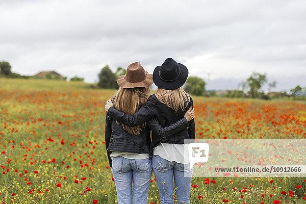 Zwei Frauen  die auf einem Mohnfeld stehen und sich umarmen.