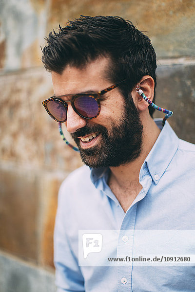 Portrait of smiling man with full beard wearing sunglasses