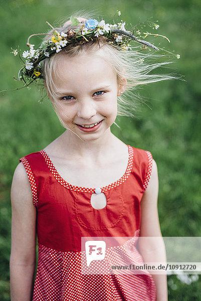 Porträt eines lächelnden Mädchens mit Blumenkranz