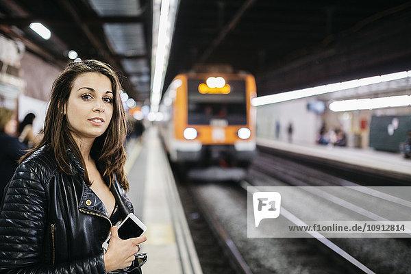 Junge Frau auf dem Bahnhof wartet auf den eintreffenden Zug