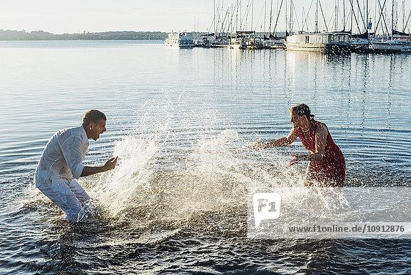 Paare  die sich gegenseitig mit Wasser bespritzen.
