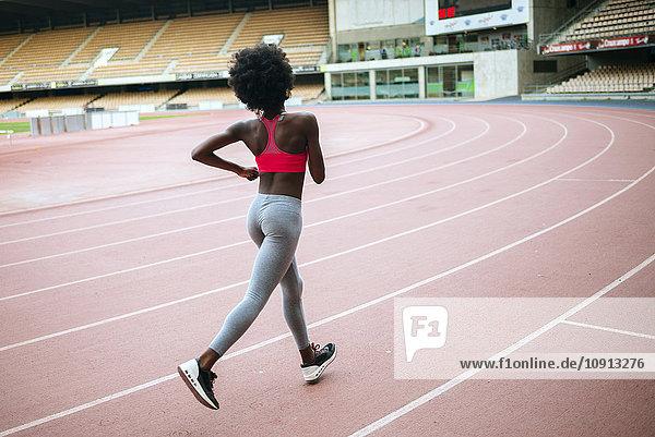 Junger schwarzer Athlet beim Laufen im Stadion