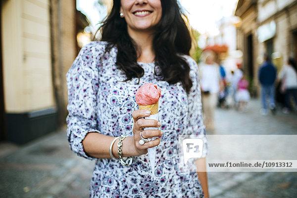 Frau hält Erdbeereis in der Hand