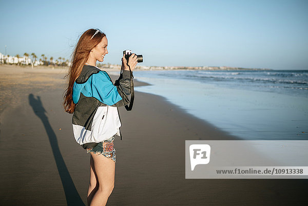 Smiling young woman using a camera on the beach