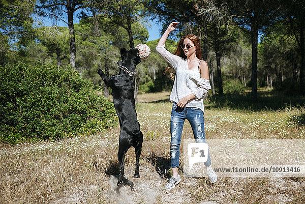 Junge Frau spielt mit ihrem Hund mit einem Ball.
