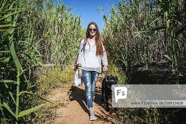 Junge Frau mit ihrem Hund in ländlicher Landschaft