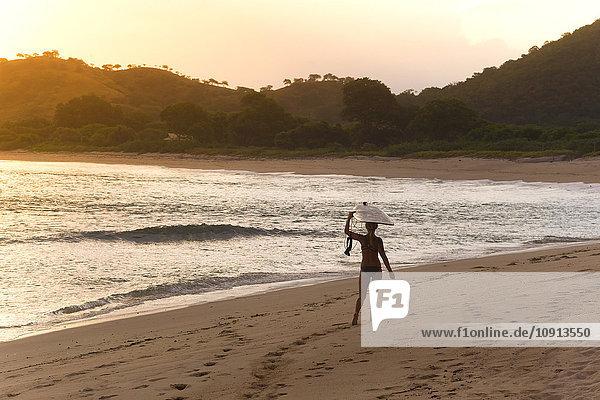 Indonesien  Insel Sumbawa  Surferin am Strand am Abend